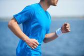 Man running along the riverbank — Stock Photo