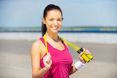 Woman in sports clothing holding jumping rope — Stock Photo