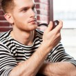 Man in striped shirt smoking pipe — Stock Photo #46902343