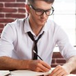 Man in shirt writing in note pad — Stock Photo #46902761