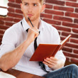 Man in shirt and tie writing in note pad — Stockfoto