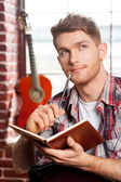 Man writing something in note pad — Stock Photo