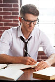 Man in shirt  writing in note pad — Stock Photo