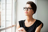 Short hair woman sitting on window sill — Stock Photo