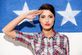 Woman posing against American flag — Stockfoto