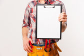 Handyman with tool belt stretching out clipboard — Stock Photo