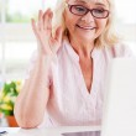 Senior woman waving abd looking at laptop — Stock Photo #47322731