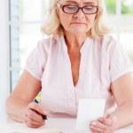 Senior woman holding bill — Stock Photo #47322977