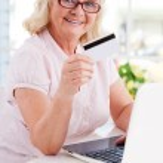 Senior woman using laptop and credit card — Stock Photo #47323007