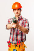 Handyman in hardhat stretching out drill — Stock Photo