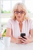 Surprised senior woman looking at mobile phone — Stock Photo