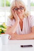Depressed senior woman looking at mobile phone — Stock Photo