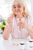 Depressed senior woman holding pill — Stock Photo