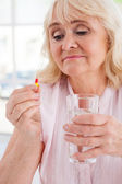 Senior woman holding pill — Stock Photo