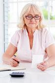 Senior woman holding bill — Stock Photo
