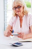 Senior woman cutting credit card — Stock Photo