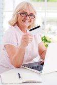Senior woman using laptop and credit card — Stock Photo