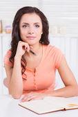 Not defteri ile masaya oturan kadın — Stok fotoğraf
