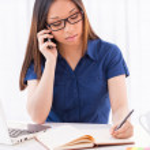 Asian woman writing in her note pad — Foto de Stock