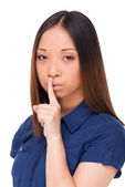Asian woman holding finger on lips — Stockfoto