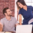 Man sitting at his working place and woman standing — Stock Photo