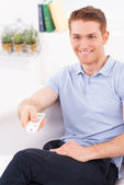 Man sitting on the couch and watching TV — Stock Photo