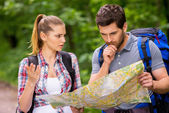 Man with backpack and woman examining map — Stock Photo