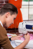 Fashion designer working on sewing machine — Stockfoto
