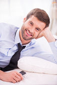Muž v košili a kravatu, ležící v posteli — Stock fotografie