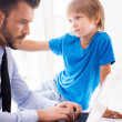 Man working on laptop with his son — Stock Photo #48113729