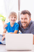 Father embracing his son using laptop — Stock Photo