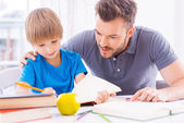 Father helping his son with homework — Stockfoto