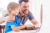 Father and son looking at the laptop — Stock Photo