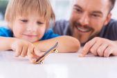 Pai olhando para filho brincando com fingerboard — Foto Stock