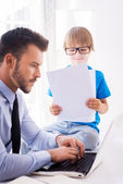 Man working on laptop with son — Stock Photo