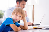 Boy holding hand in hair while  busy father working — Stock Photo