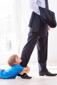 Boy embracing his father leg — Stock Photo