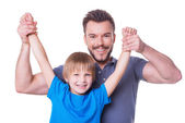 Father carrying his playful son by hands — Stock Photo
