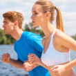 Woman and man running along the riverbank — Stock Photo #48420207