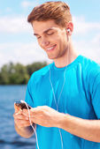 Sporty man with smart phone — Stock Photo