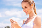 Woman in sports wear with smart phone — Stock Photo