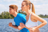 Woman and man running along the riverbank — Stock Photo