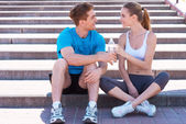 Couple in sports clothing sitting on stairs — Stock Photo