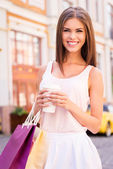 Woman holding shopping bags and cup of drink — Stock Photo