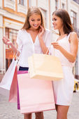 Woman showing her friend shopping bag — Стоковое фото