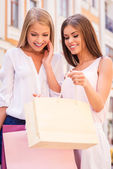 Woman showing her friend shopping bag — Stock Photo