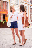 Women walking along the street and talking — Stock Photo