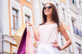 Woman in sunglasses carrying shopping bags — Stock Photo