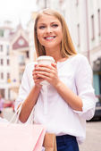 Woman holding shopping bags and cup — Stock Photo