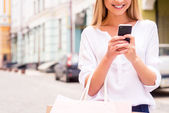 Woman holding shopping bags and mobile phone — Stock fotografie